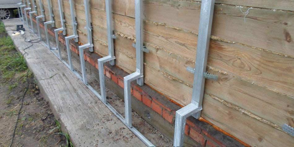 После полной очистки фасадной поверхности следует по периметру деревянного дома установить каркас обрешётки