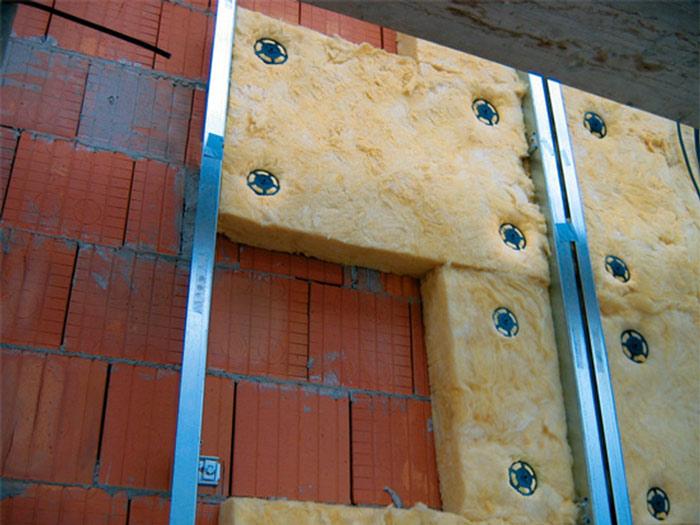 Дома со стенами из кирпича обустраиваются утеплителем под сайдинг несколько иначе, чем строения из дерева. Следует отдать предпочтение обрешётке на основе металлопрофиля, который вывешивается на специальных креплениях