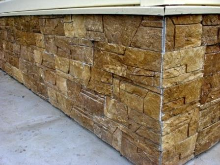 Использование натурального декоративного камня для отделки цоколя сочетается с любой облицовкой